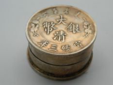A Chinese coin topped box. 3.75 cm diameter.