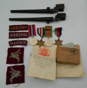 A collection of British Airborne WWII medals and box, with papers and uniform patches, etc.