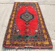 A Persian red ground rug. 91 x 44.5 cm.