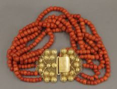 An 18 ct gold clasp and coral necklace. 36 cm long. 324 grammes total weight.