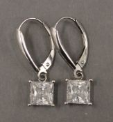 A pair of 14 K white gold earrings. Each 6 mm wide.