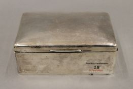 A silver cigarette box. 14 cm wide. 17.8 troy ounces total weight.