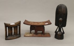 Two African tribal head rests and a carved figure. The latter 29 cm high.