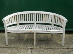 A curved wooden garden bench