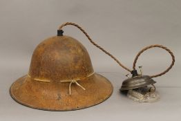 A Belgian military helmet, converted to a hanging lamp. 29 cm wide.