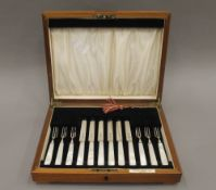 A set of six mother-of-pearl handled fruit knives and forks, with hallmarked silver blades,