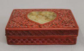 A cinnabar and jade box. 14.5 cm wide.