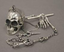 A white metal skull on chain. The skull 2 cm high.