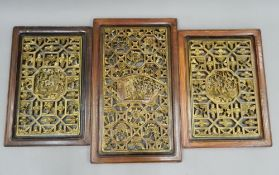 Three Chinese gilt heightened pierced and carved wooden panels. The largest 48.5 x 81 cm.