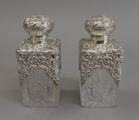 A pair of silver topped cut glass scent bottles. 14.5 cm high.