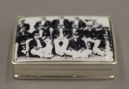 A silver snuff box, the lid inset with a cricket team. 5 cm wide.