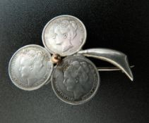Three Dutch silver coins formed into a brooch. 3.5 cm wide.