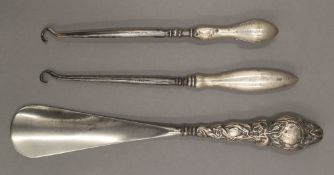 A silver handled shoehorn and two silver handled button hooks. The former 22 cm long.