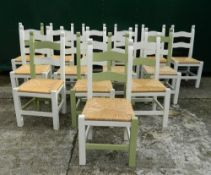 A set of fourteen modern painted rush seated dining chairs. Each 47 cm wide.