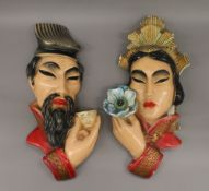 A pair of plaster wall masks depicting a Chinese man and woman.