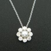 An 18 ct white gold diamond and pearl pendant, on an 18 ct white gold chain.