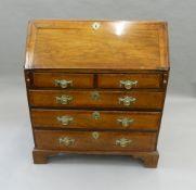 A George III oak crossbanded bureau. 94.5 cm wide.