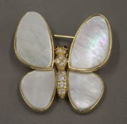 An 18 K gold mother-of-pearl and diamond set butterfly brooch. 3.5 cm wide.