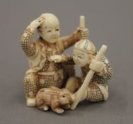 A late 19th/early 20th century Japanese carved ivory netsuke of two boys playing with a rabbit. 3.