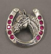 A sterling silver horse's head brooch. 3 cm wide.
