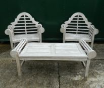 A pair of Lutyens style wooden garden chairs and a table