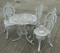 A round garden table and three metal garden chairs