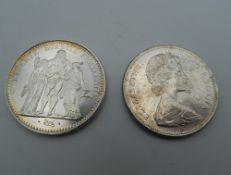 A French silver 10 Franc coin and a Canadian coin