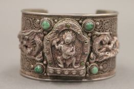 An unmarked Tibetan silver and turquoise bangle. 7 cm wide.