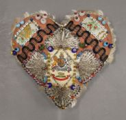 A vintage heart shaped pin cushion. 19 cm wide.
