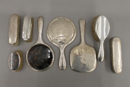 A quantity of silver backed brushes and mirrors