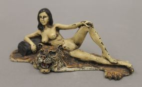 A cold painted bronze model of a nude lady on a tiger skin rug. 15 cm wide.