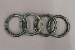 Four jade bangles. Each 7.5 cm wide.