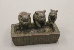 A small bronze model of three pigs at a trough. 4.5 cm wide.