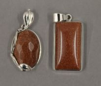 Two silver goldstone pendants. The largest 3 cm high.