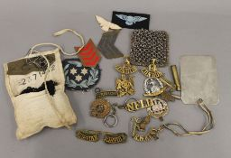 A quantity of military cap badges, buttons, etc.