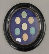 Seven seals, housed in a black oval frame. 25 cm high.
