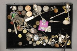 A display case containing Georgian/Victorian coins, vintage badges, hatpins, spoons, etc.