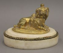 A 19th century gilded bronze figure of a recumbent dog, on a marble plinth base. 11 cm wide.