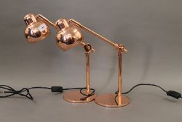 A pair of small copper anglepoise lamps