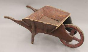 A 19th century child's wheelbarrow. 74 cm long.