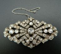 An unmarked white gold or platinum diamond set brooch of pierced navette form,
