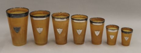 A cased set of seven silver rimmed horn beakers. 17 cm high.