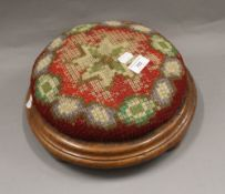 A Victorian squat stool on bun feet, with tapestry covered cushion. 30 cm diameter.