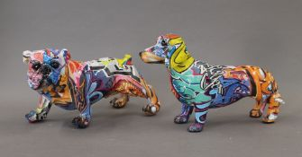Two graffiti decorated dogs. The largest 25 cm long.