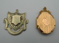 A 9 ct gold front and back locket and a Durban silver fob. The former 3.5 cm high.
