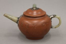 A Chinese Yixing teapot with jade mounts. 10 cm high.