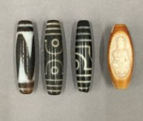 Four Tibetan beads. The largest 5.5 cm wide.