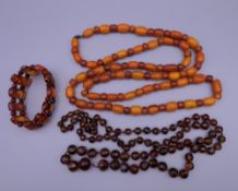 An amber bead necklace, a bracelet and a facet cut glass necklace.