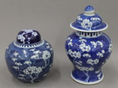 Two 19th century Chinese blue and white 'prunus blossom' vases and covers. The tallest 28 cm high.