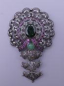 A vintage pendant set in silver and gold with rubies, diamonds and emeralds. 7 cm high.